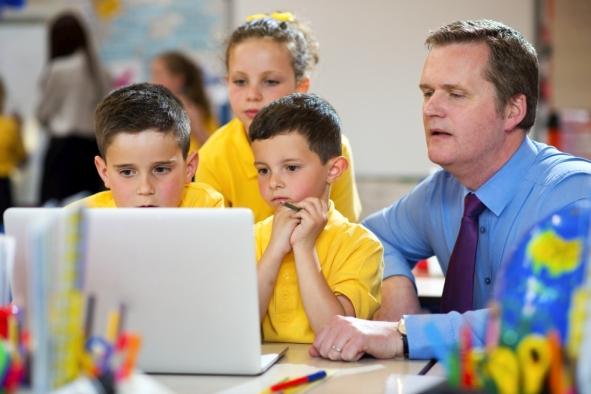 primary schoolchildren looking at a laptop in school with his teacher